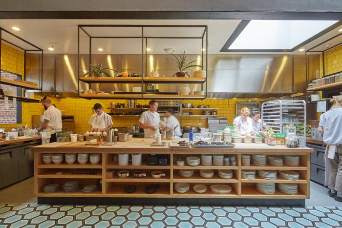 The bold, sunshine-yellow tile lining the kitchen speaks to Chef Ravi Kapur's Hawaiian roots. (Photo credit: Studio Terpeluk)
