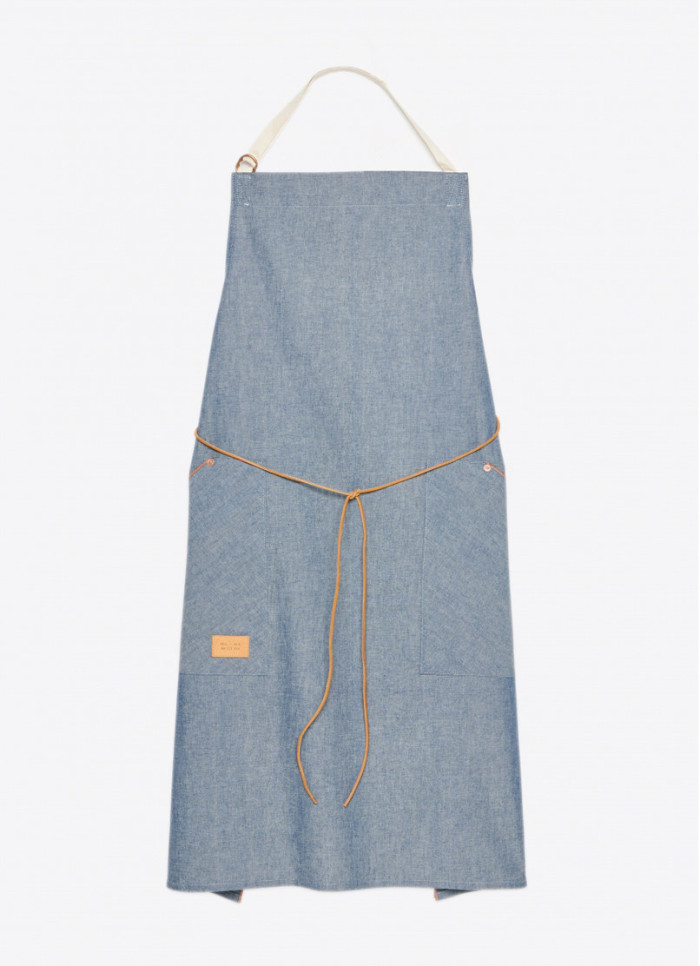 The apron was designed with lightweight orange line selvedge denim, deep pockets accented with copper rivets, a leather tie, and adjustable neck strap. (Photo credit: Billy Reid)