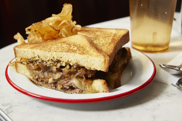 The patty melt comes smothered in everything bagel spiced sauce.